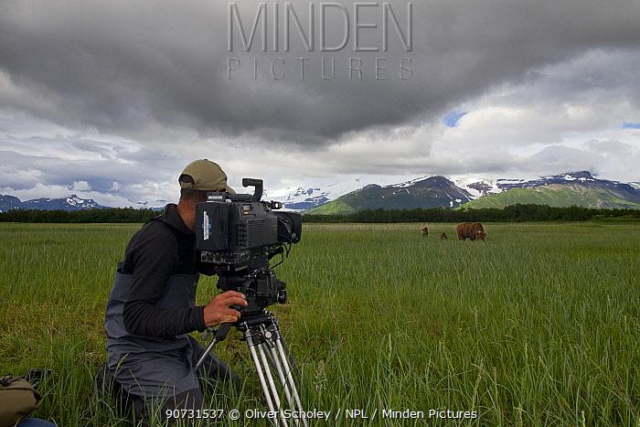 Cameraman filming Grizzly bear (Ursus arctos horribilis) with cubs on production for 'Bears'. Katmai National Park, Alaska, July 2013.