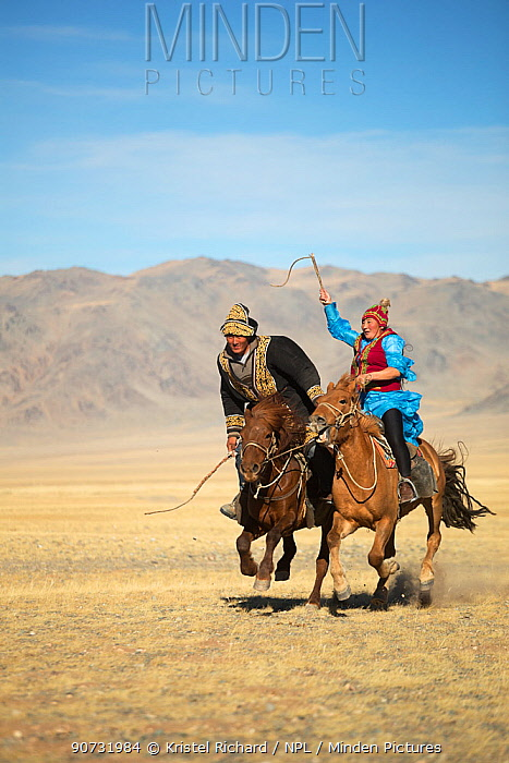 Eagle hunter woman whipping man on slow Mongolian horse to try to slow him down during game at the Eagle hunter's festival. She is on a faster horse but if he wins the game he is entitled to a kiss. Eagle Hunters Festival, near Sagsai, Bayan-Ulgii Aymag, Mongolia. September 2014..