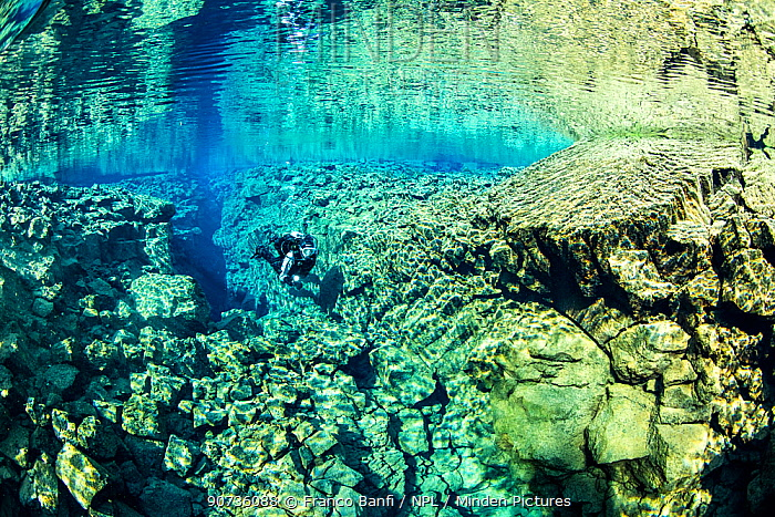 Scuba diver runs through Silfra Hall, a 200 meters up and down swim that leads to Silfra Cathedral, Thingvellir National Park, Iceland.