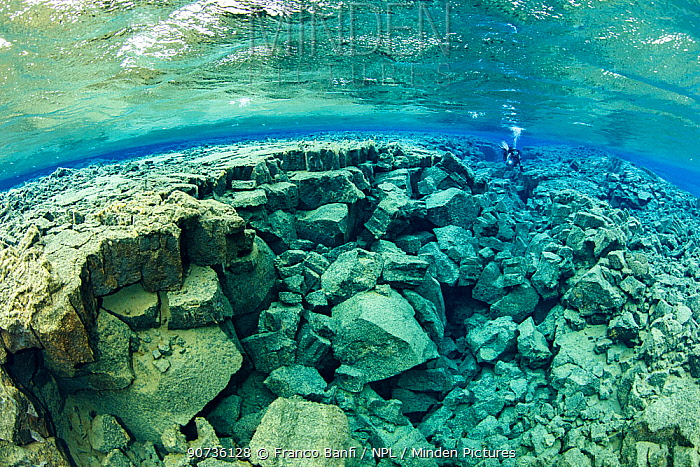 Scuba diver exploring Little Crack, almost like a miniature version of the main fissure, with both deep and shallow sections and many tunnels, Silfra Lagoon, Thingvellir National Park, Iceland.