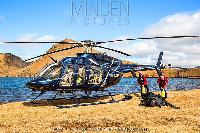 Heli-diving, downloading the scuba diving equipment from the helicopter on a mountain lake, Iceland