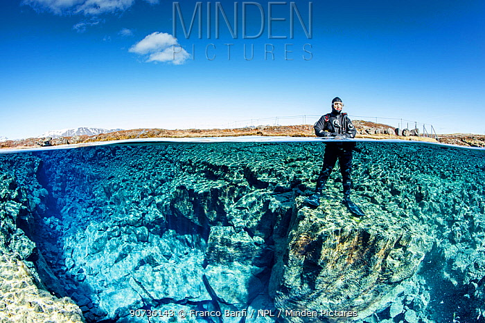 Split level view of man posing on the edge of Little Crack, situated on the left hand side of Silfra Lagoon, Thingvellir National Park, Iceland.