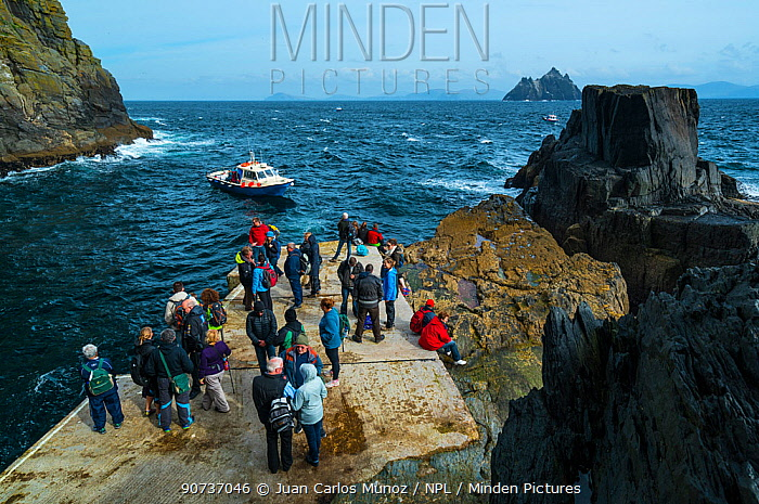 People standing on harbour wall at Skellig Michael, Skellig Islands World Heritage Site, County Kerry, Ireland, Europe. September 2015.