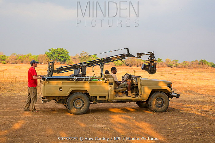 Wildlife cameraman Jamie McPherson, on filming vehicle - with 4K gyro stabilised cineflex suspended from a jib arm. On location to film BBC series 'The Hunt'. South Luangwa National Park, Zambia. Novemeber 2014.