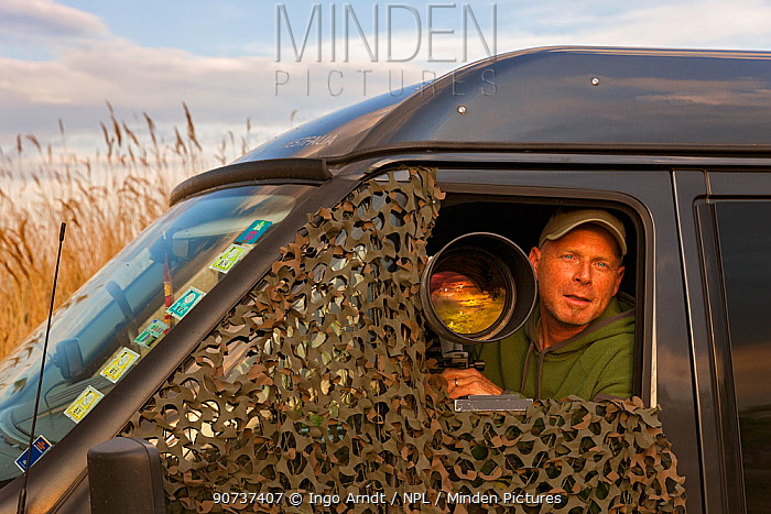 Wildlife Photographer Ingo Arndt on location, taking pictures of birds with telephoto lens out of his car. Lake Neusiedl, Austria , April.