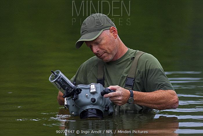 Wildlife Photographer Ingo Arndt preparing camera in underwater-housing to photograph European Beavers (Castor fiber) , Spessart, Germany, June.