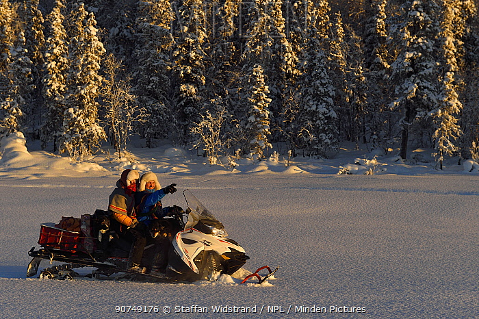 Nils-Torbjorn Nutti, owner and operator at Nutti Sami Siida, and Klara Enbom-Burreau on snowmobile trip into the wilderness, Jukkasjarvi, Lapland, Laponia, Norrbotten county, Sweden Model released.
