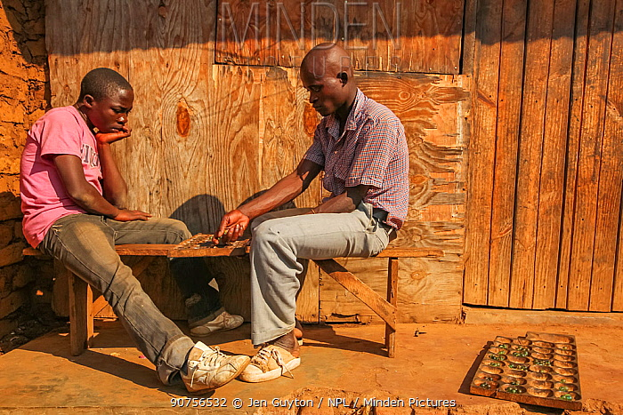 Two young men play a game called Bao in the back alleys of a marketplace in Lilongwe, Malawi.