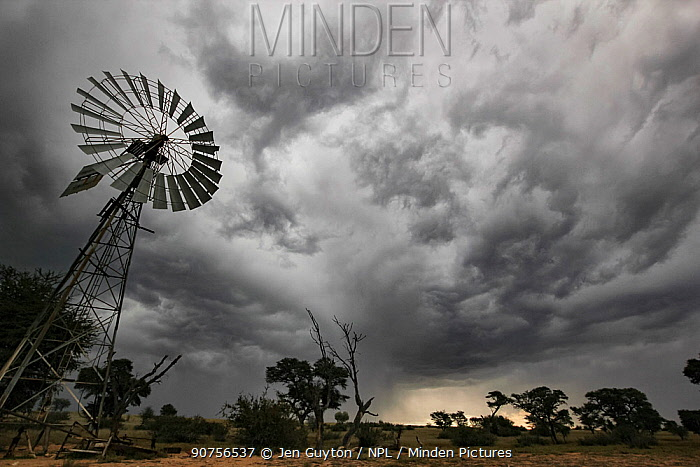 Windmill under a gathering thunderstorm in the Kalahari Desert, South Africa. These traditional windmills are still used to raise groundwater for use in the home and to fill animal troughs. May 2011