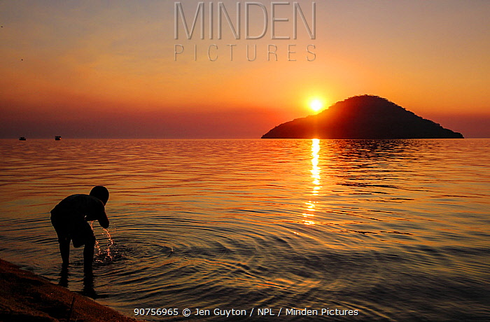 Boy washing his face in Lake Malawi  at sunset., Cape Maclear, Malawi  June 2011
