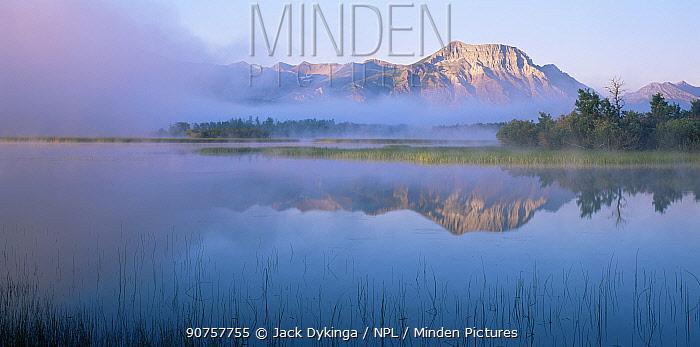Vimy Peak and fog reflected in calm water of Lower Waterton Lake, dawn, Waterton Lakes National Park, Canada
