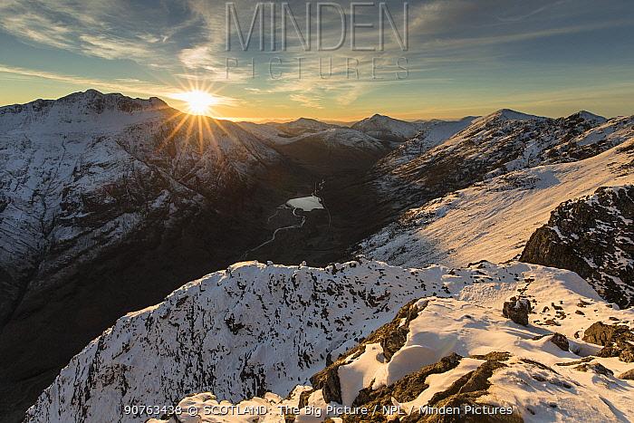 Sunset over snow covered mountains, view north west along Aonach Eagach ridge towards Glen Coe, Lochaber, Scotland, UK, November 2016