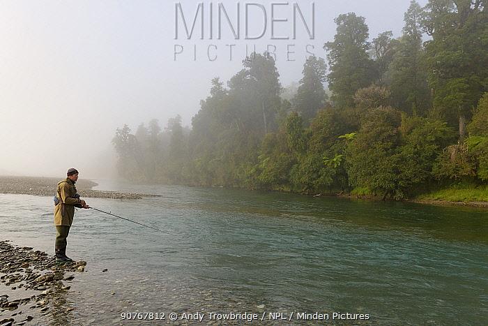 Salmon fisherman on a misty river. West Coast, South Island, New Zealand. February. Model Released.