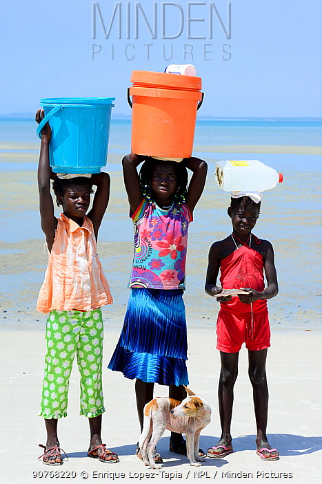 Portrait of three girls, with containers on head  to collect water, and dog, Orango Island, Bijagos UNESCO Biosphere Reserve, Guinea Bissau, February 2015.