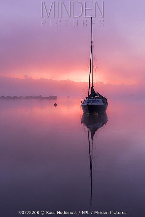Boat reflected on Wimbleball reservoir, sunrise with mist, Exmoor National Park, UK. October 2017.