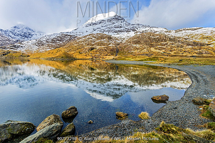 Crib Goch (Red ridge) part of the Snowdon horseshoe, covered in snow reflected in Llyn Llydaw, with the summit of Mount Snowdon. Snowdonia National Park, North Wales, UK, March 2017.