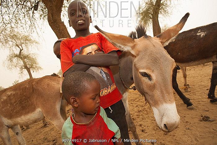 Two Ouled Rachid boys with domestic donkeys, Bon Village, Zakouma National Park, Chad, 2010.