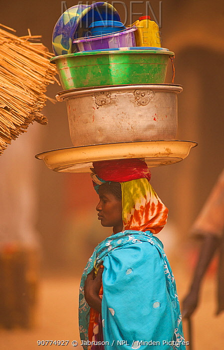 Ouled Rachid tribeswoman carying bowls and buckets on her head, Kashkasha village near Zakouma National Park, Chad, 2010.