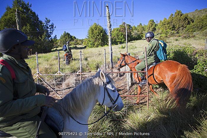 Wildlife poaching horseback patrol unit ride through gate to enter Mount Kenya National Park, Kenya