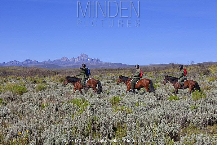 Wildlife poaching patrol unit on horseback with Mount Kenya in background, Mount Kenya National Park, Kenya