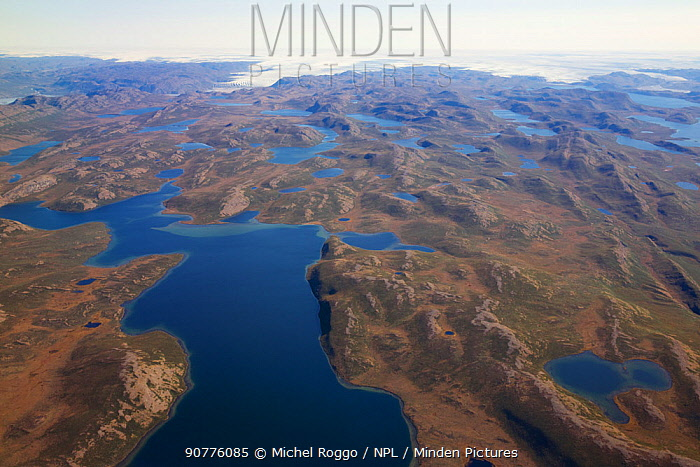 Aerial view of the landscape of the south-west coast of Greenlandbetween Kangerlussuaq and Ilulissat, with glaciers stretching out of the ice shield towards the sea.  Ilulissat Icefjord UNESCO World Heritage Site, Greenland. August 2014. Photographed for The Freshwater Project