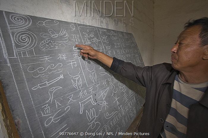 Man pointing at Naxi pictograph character written on blackboard, Yunnan, China