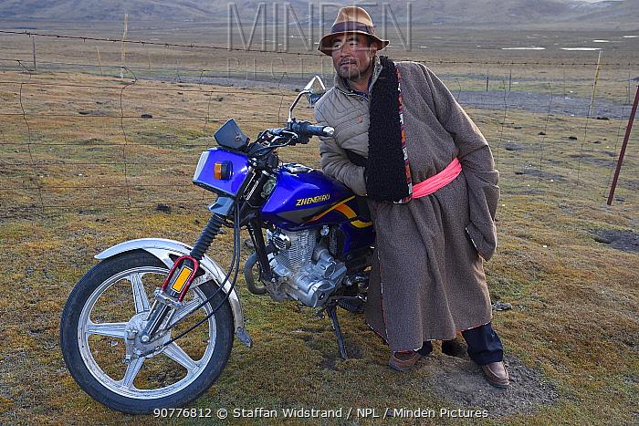 Tibetan shepherd and his motorbike, Tibetan Plateau, Qinghai, China October 2016.
