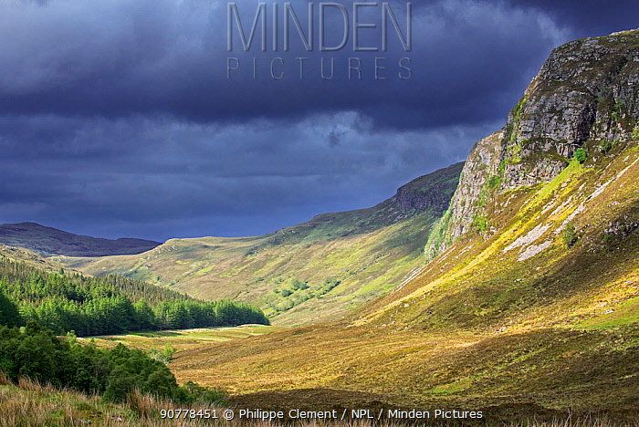 Mountain scenery showing dark rain clouds rolling in over sunny hillside and valley in Wester Ross, Scottish Highlands, Scotland, UK, May 2017