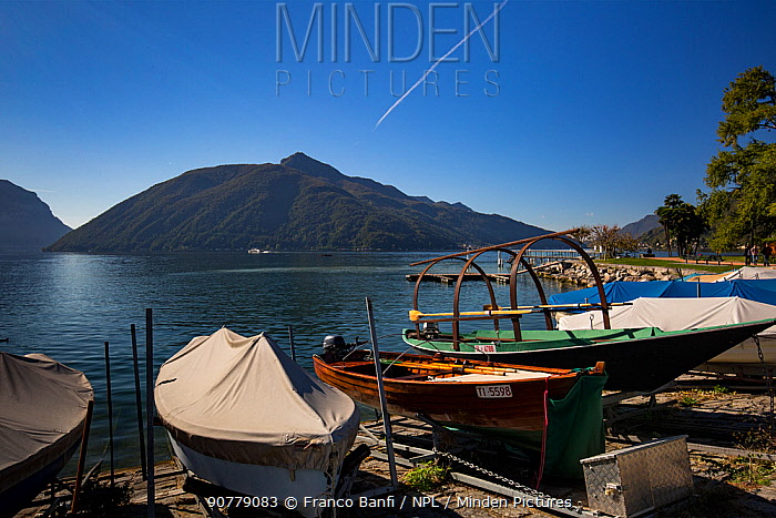 Local boats on Lake Lugano with Monte San Giorgio in the background, a UNESCO World Heritage Site, Ticino, Switzerland. October 2017.