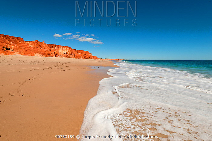 Beach waves on the white sands. Spectacular views of ochre-coloured earth and sandstone cliffs, white sands and aquamarine waters of the Dampier Peninsula is one of the most spectacular coastal environments in Australia and a great place to encounter the Kimberley's indigenous culture, Broome, Western Australia, Australia July 2016.