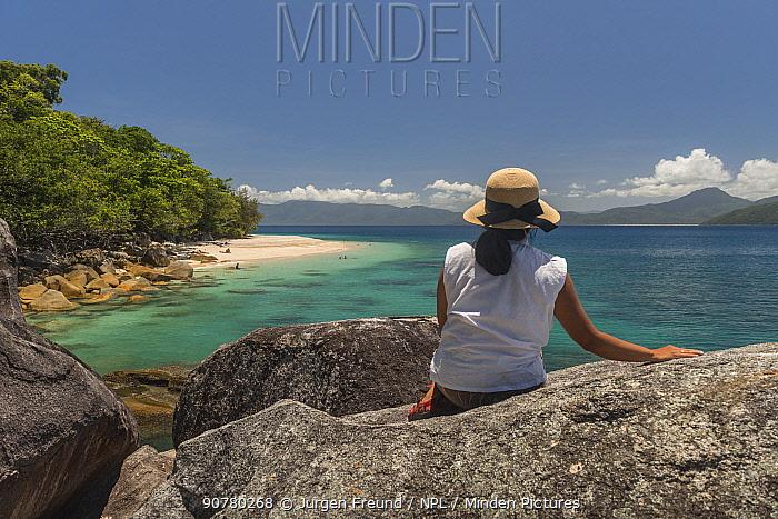 Rear view of woman sitting on rocks, Fitzroy Island, Tropical Far North Queensland, Australia. December 2015. Model released.