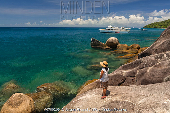 Woman on rocks, Fitzroy Island, Tropical Far North Queensland, Australia. December 2015. Model released.
