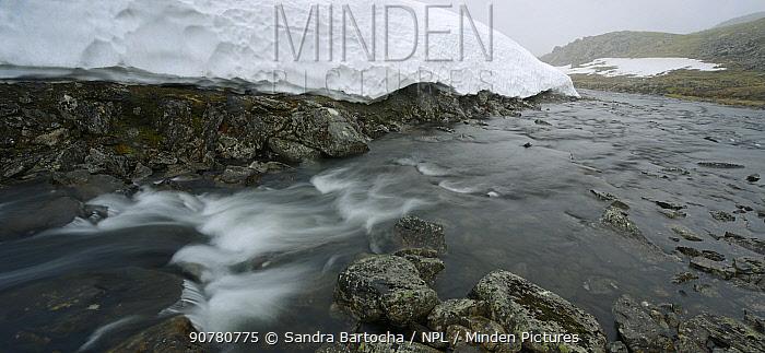 Stream through tundra and snow cornice, Nordkinn Peninsula, Norway