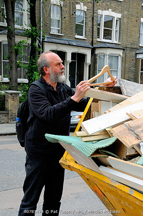 Man looking at clothes hanger he's found in skip, Highbury, London Borough of Islington, UK