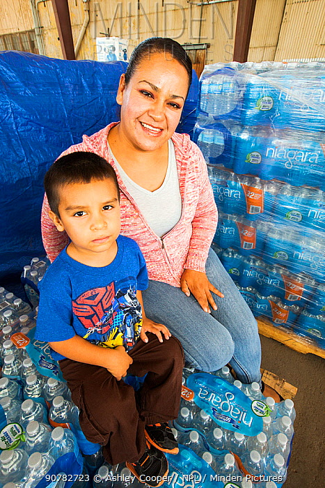Mother and child with bottled water supplied from water charity in Porterville to people who have had no running water for five months. California, USA, October 2014.