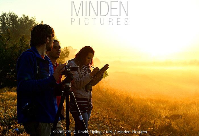 Maltese bird watchers at dawn monitoring migration and hunting during BirdLife Malta Springwatch camp, April 2013