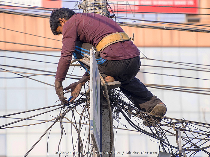 Electrician works on a tangle of electric wires in Kathmandu, Nepal. December 2012.