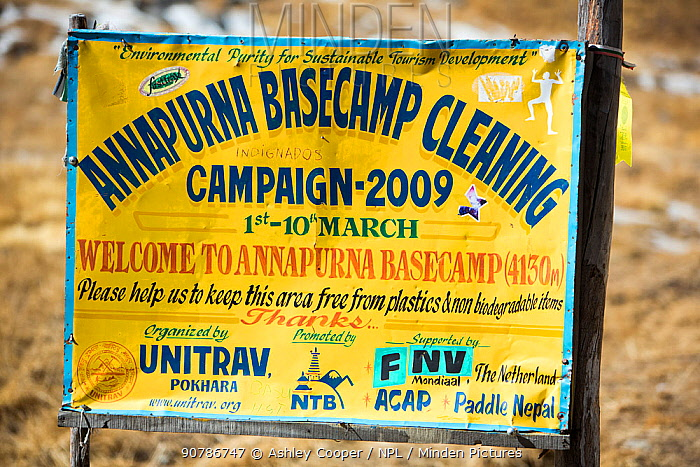 Annapurna base camp at 4130 metres in front of Annapurna South summit, , with a sign about a cleanup campaign. Annapurna Sanctuary, Himalayas, Nepal. December 2012.