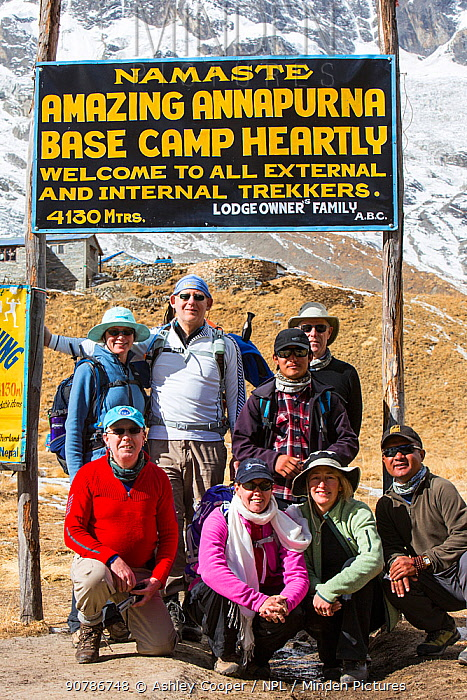 Trekking group at Annapurna base camp at 4130 metres in front of Annapurna South summit, Annapurna Sanctuary, Himalayas, Nepal. December 2012.