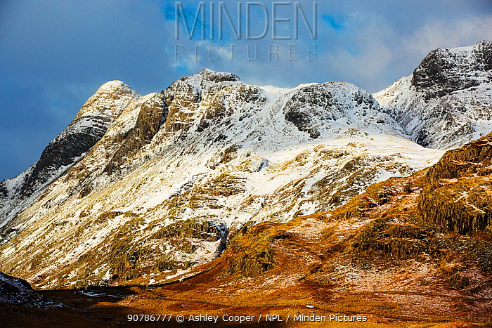 The Langdale Pikes from Blea Tarn. With a car driving over the Blea Tarn road into Little Langdale, Lake District, England, UK, January.