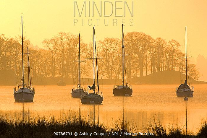 Sunrise over sailing boats on Lake Windermere in Ambleside, Lake District, England, UK. December 2014.