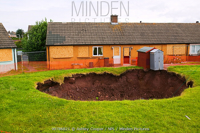 Sinkhole  in a back garden in Egremont Cumbria as a result of mining subsidence when an old mine shaft opened up, England, UK. June 2005