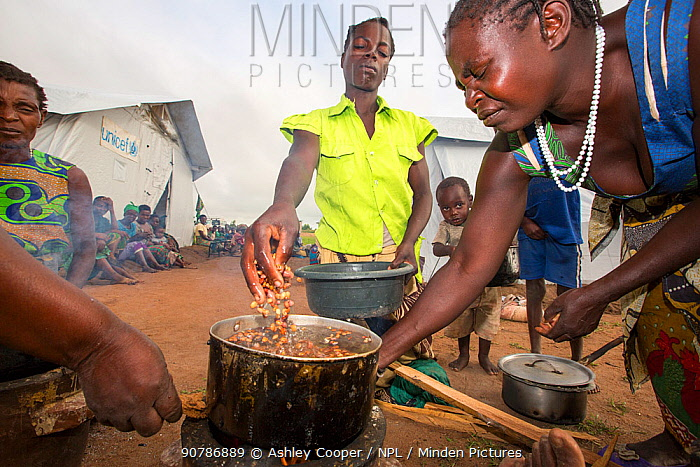 People displaced by flooding at  Chiteskesa refugee camp,  cooking on a fuel efficient stove.  near Mulanje, Malawi. March 2015.