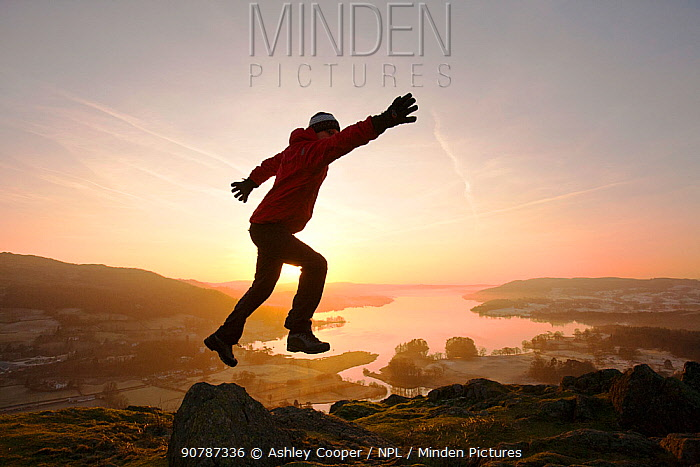 Man leaping at sunrise,  Lake Windermere from Todd Crag above Ambleside, Lake District, England, UK. January 2012
