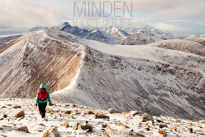 The view west into the Cuillins from Beinn na Caillich summit, behind Broadford on the Isle of Skye, Scotland, UK, with a middle aged woman walker. February 2012