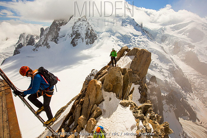 Mont Blanc with climbers on the Cosmiques Arete, climbing the ladder to access the cable car station. Aiguille Du Midi above Chamonix, France,  September 2014