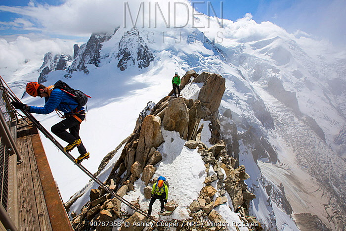 Mont Blanc from the Aiguille Du Midi above Chamonix, France, with climbers on the Cosmiques Arete, climbing the ladder to access the cable car station. September 2014