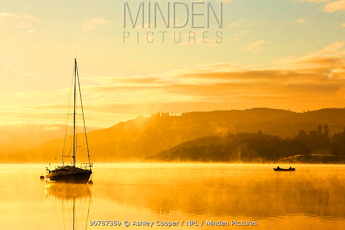 Sunrise over men fishing in a boat on Lake Windermere in Ambleside, Lake District, UK. December 2014