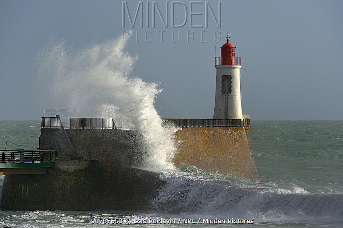 Wave crashing against wall with lightouse, La Chaume, Les Sables d'Olonne, Vendee, France. January