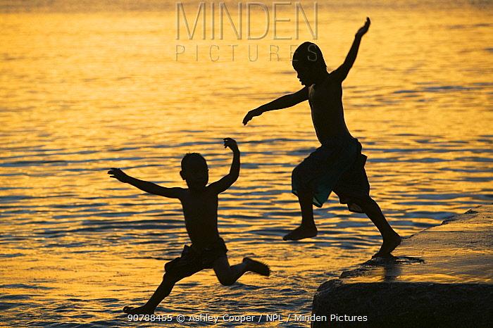 Tuvaluan children leaping into the sea on Funafuti Atoll, Tuvalu. March 2007